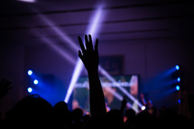 silhouette of a raised hands and spotlights at a concert