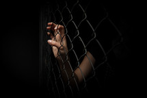 hands gripping a chain link fence