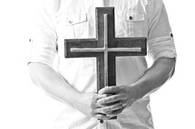 man holding a cross in front of his chest