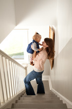 mother holding her toddler daughter standing in a stairway