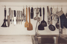 utensils hanging in a kitchen over a sink