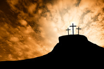 silhouettes of three crosses on a mount at sunrise