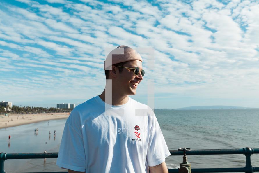 a man in a beanie standing on a beach