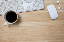 computer keyboard, computer mouse, earbuds, and coffee mug