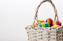 colored chocolate easter eggs in a wicker basket