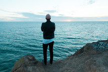 a man in a beanie standing on rocks along a shore