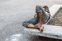 a homeless man sleeping on a concrete bench
