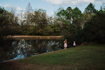 sisters standing by the edge of a pond