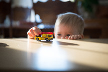 toddler boy with a toy firetruck