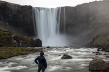 a woman watching a waterfall in Iceland