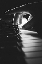 A b&w shot of a man's hand playing a chord on the keyboard