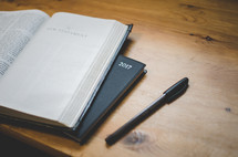 a bible open at the new testament next to a 2017 diary planner and pen