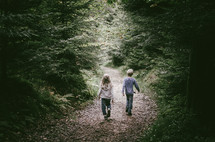 a boy and girl on a forest path