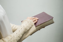 a woman standing holding a Bible