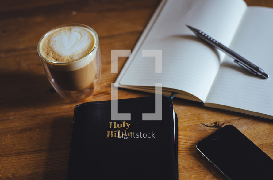 A coffee, phone, notebook, pen and bible on a table