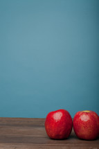 Two red apples on a wooden surface with a blue background.