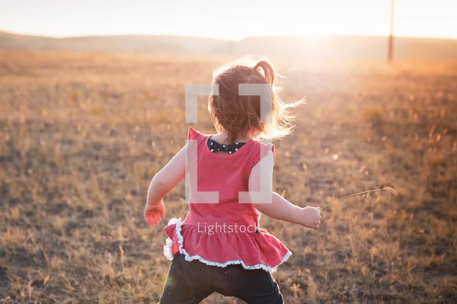 toddler girl running in a field