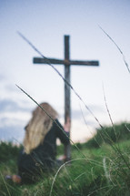 Woman kneeling in worship at a wooden cross in a field of grass.