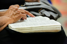 A elderly woman's hand holding a pen at a Bible study