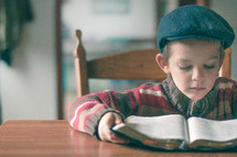 Boy sitting at the table reading his bible
