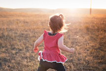 toddler girl running in a field