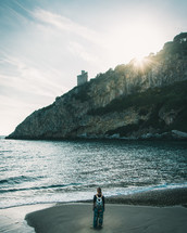 a girl with a backpack standing on a beach shore at sunrise