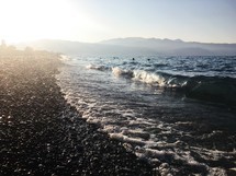 waves washing onto a rocky shore in Greece
