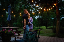 a couple standing on a backyard deck in summer