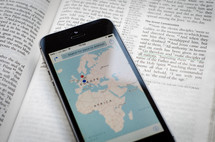 A phone with a world map showing Europe & Africa sitting on a bible open to the great commission