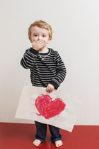 boy child with his hands over his mouth holding a Valentines picture