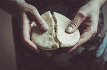 A woman breaking a piece of bread.