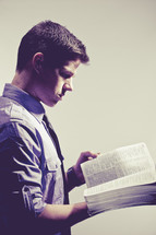 man reading a Bible against a white background