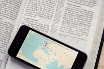 A phone with a world map showing Europe, Africa & Asia sitting on a bible open to the great commission