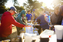 teens getting food at an outdoors luncheon