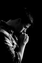 man kissing his knuckles in prayer