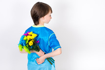 Boy holding a bouquet of flowers behind his back.