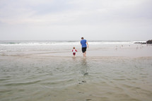 father and toddler son walking in water at the beach