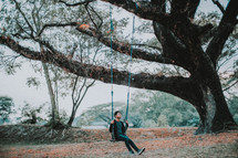 a man on a swing hanging from a tree