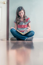 Girl sitting on the floor reading her bible