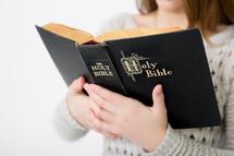 A teen girl reading a Bible