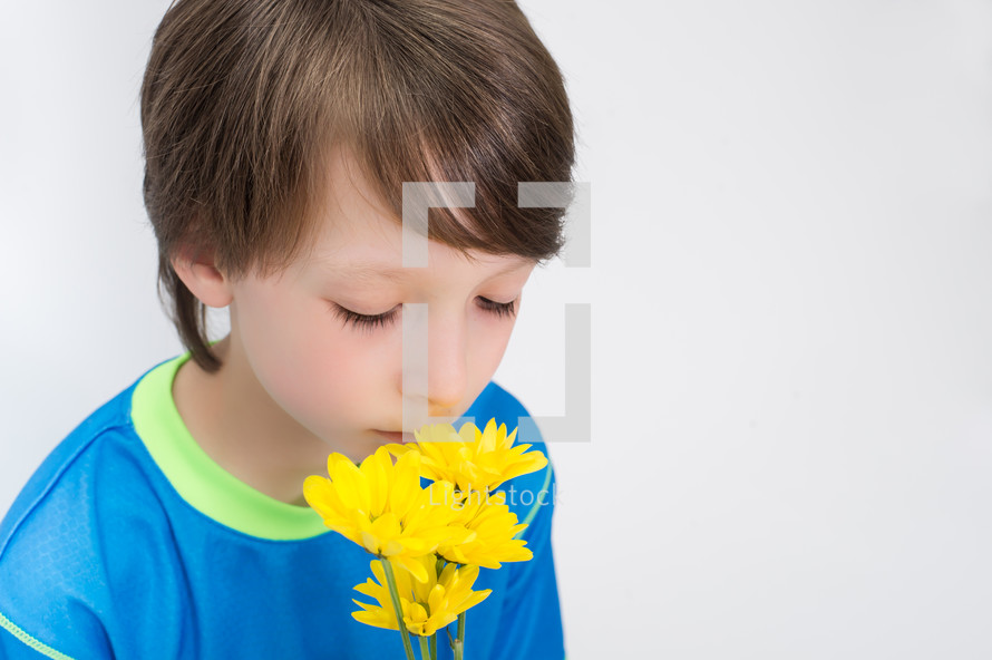 Boy smelling flowers.