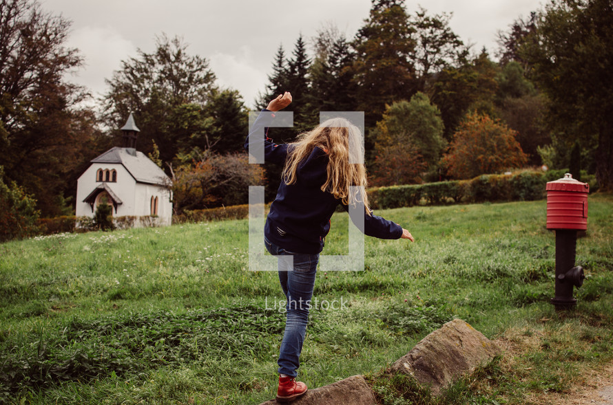 A girl balances on some rocks with a small country church chapel in the background