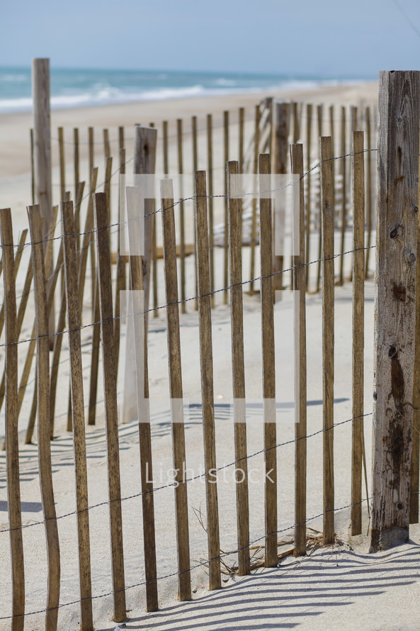 Reed fence on beach at ocean.