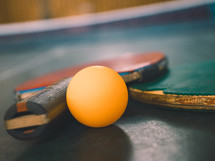 two ping-pong bats and ball on a table tennis table
