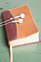 earbuds resting on a Bible