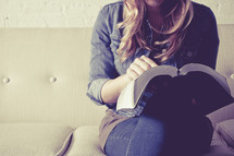 woman sitting on a couch reading a Bible