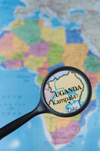 magnifying glass over a map of Uganda