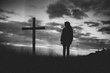 Silhouette of a person standing by a cross in a field at sunrise.