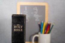 Holy Bible, colored pencils in a mug, and a blackboard