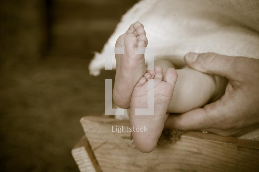 feet of baby Jesus lying in a manger